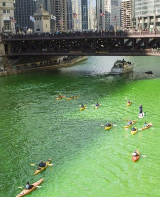 Kayakers paddle along a bright-green river during the annual dying of the Chicago River for St. Patrick's Day celebrations. 3/14/2015